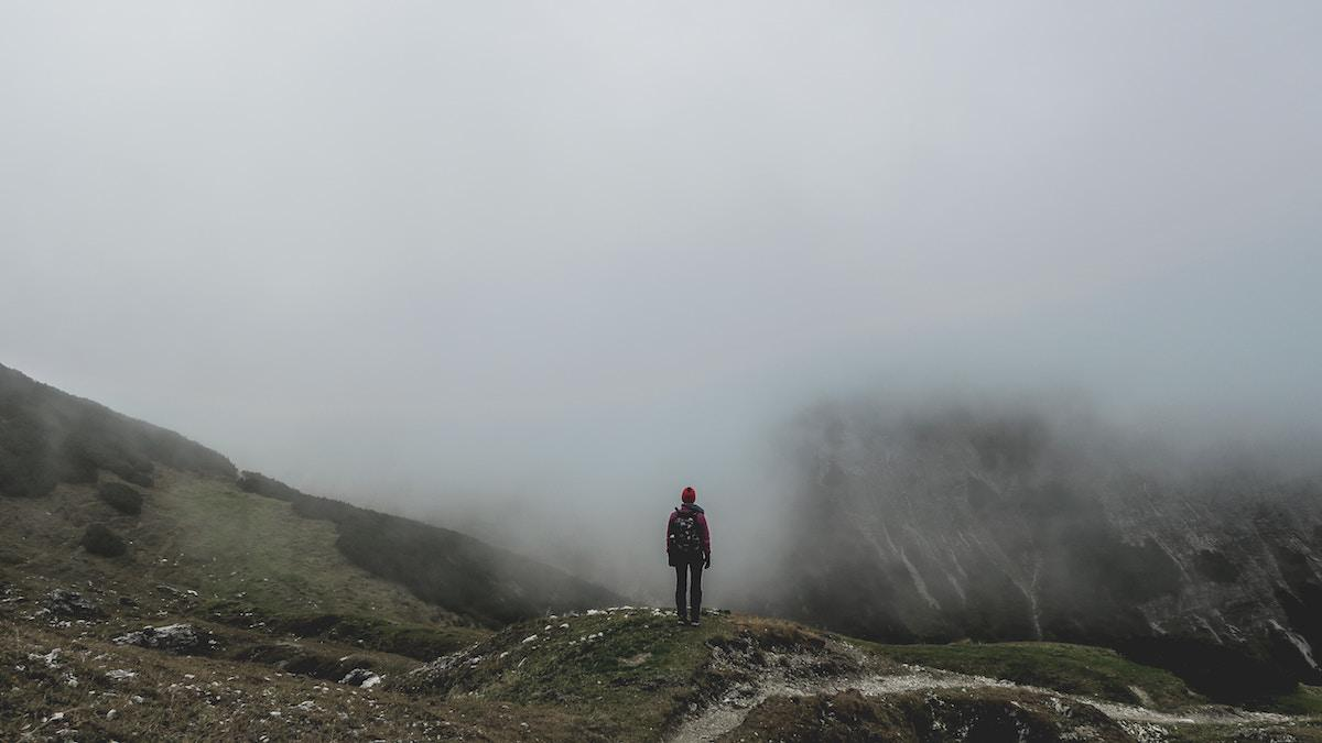 Lonely person standing on a mountain surrounded by fog