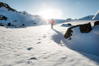 Mountaineer walking through the snow into the sun